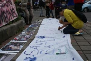 Warga Batu membubuhkan tandatangan sebagai tanda mendukung penyelamatan sumber air di Batu, Minggu (17/3/2013).