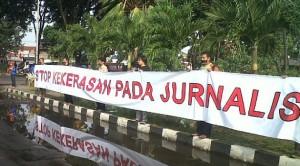 aktivis AJI Surabaya membentangkan spanduk keprihatinan, di depan markas Polda Jatim, Jumat (28/6). (foto:lensaindonesia)